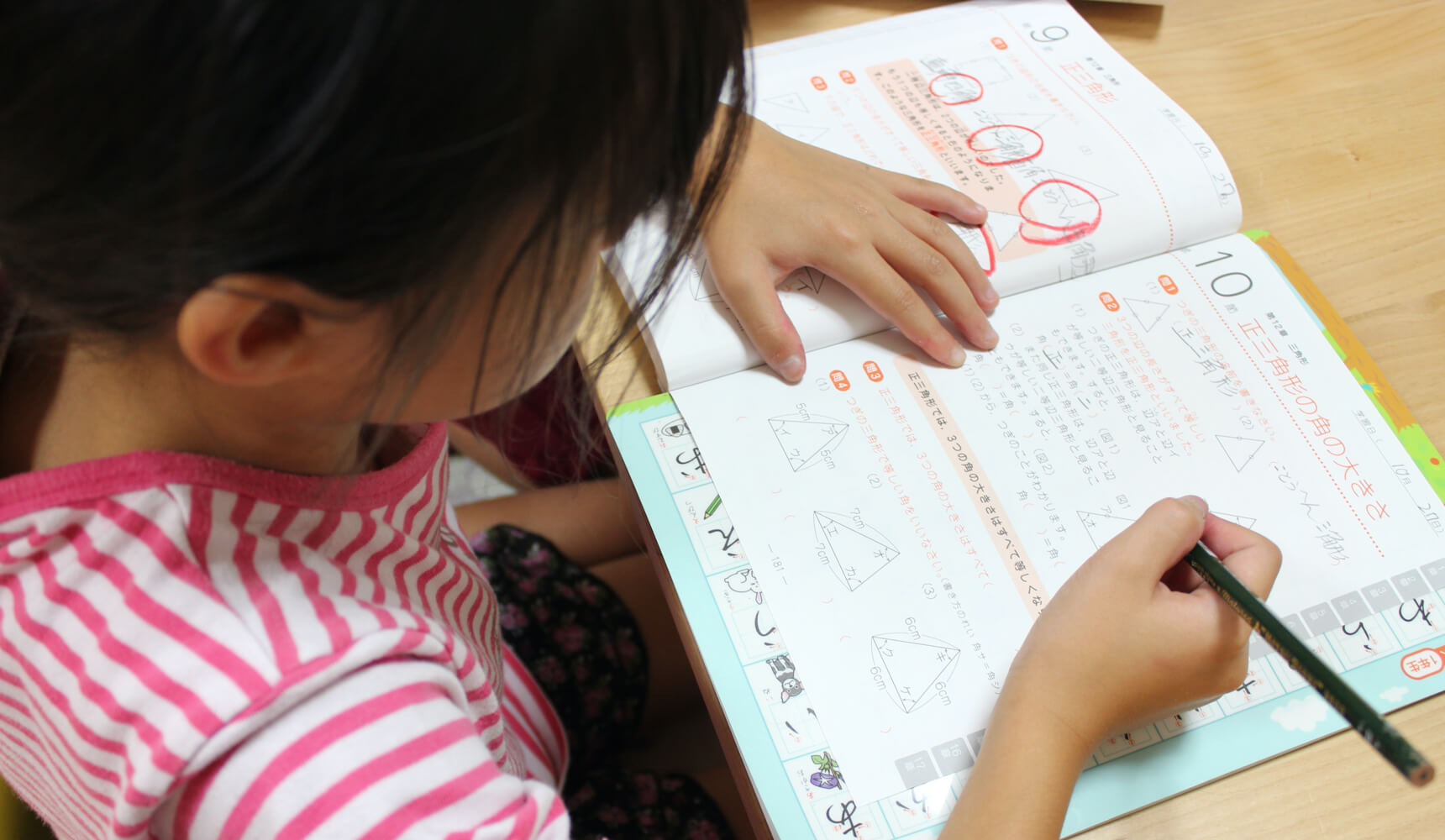 A young child in a red and white striped t-shirt sits at a desk and writes in a notebook
