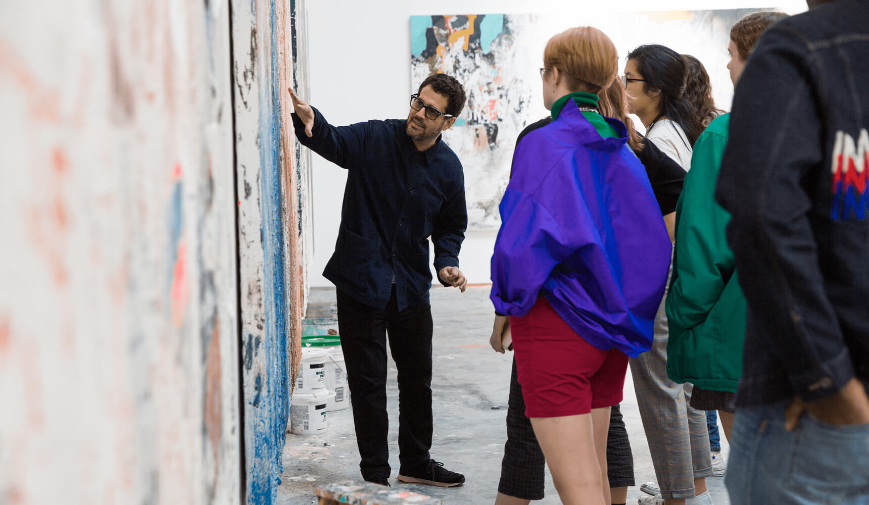 A man wearing a black shirt and black pants points to a piece of art while a group of young people look on.