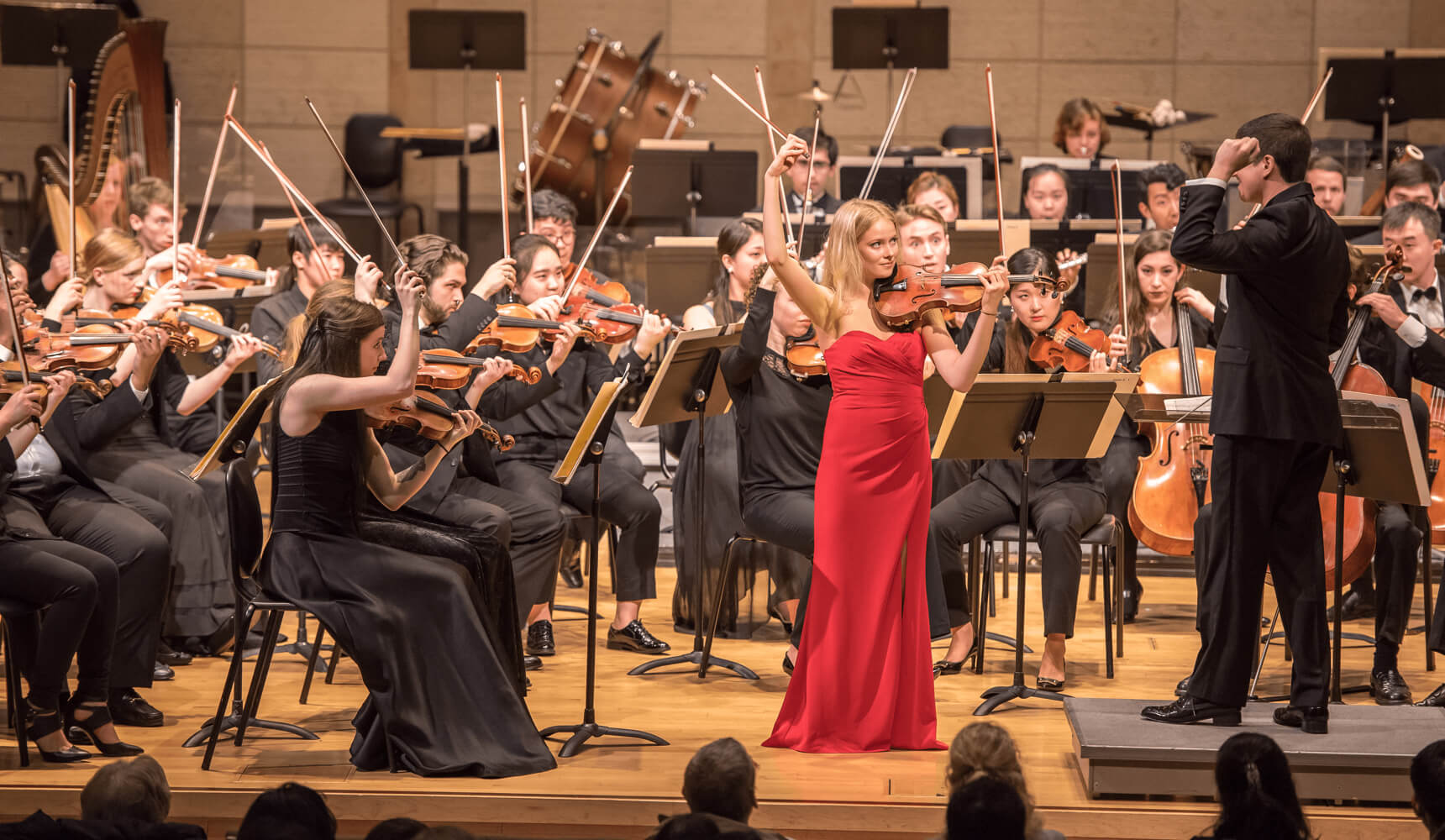 A symphony performs while a violin soloist plays in the center wearing a red dress
