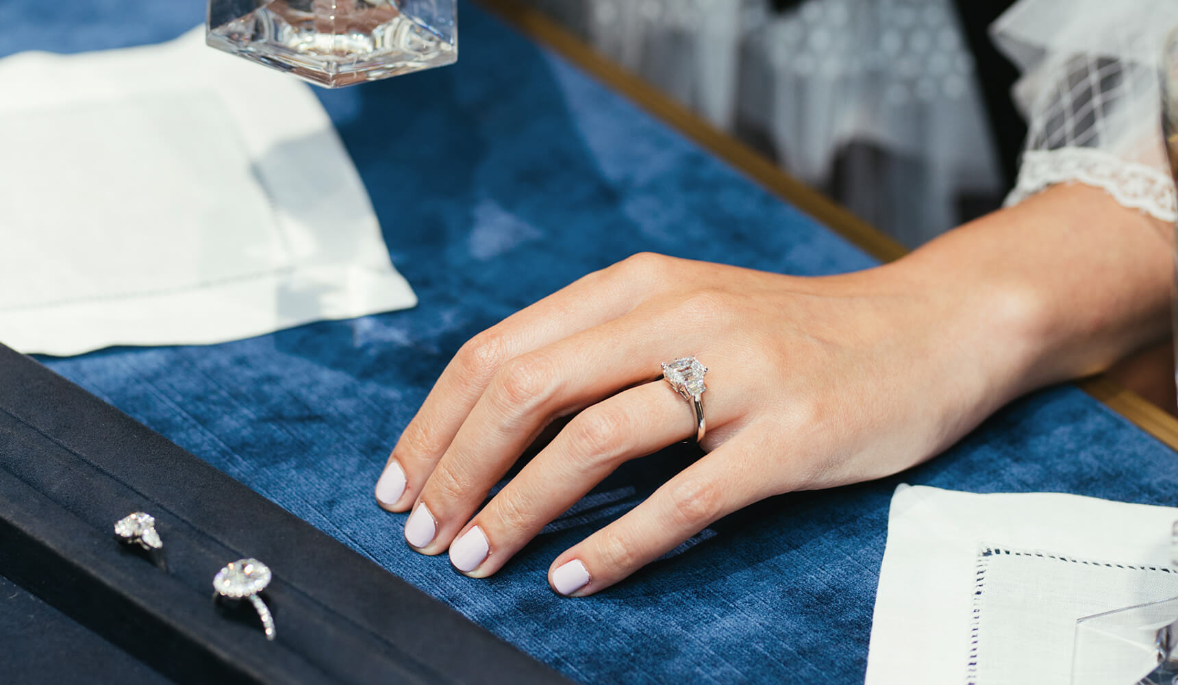 Woman's hand wearing a Harry Winston Classic Winston Emerald-Cut Diamond Engagement Ring next to a tray of Harry Winston Diamond Engagement Rings