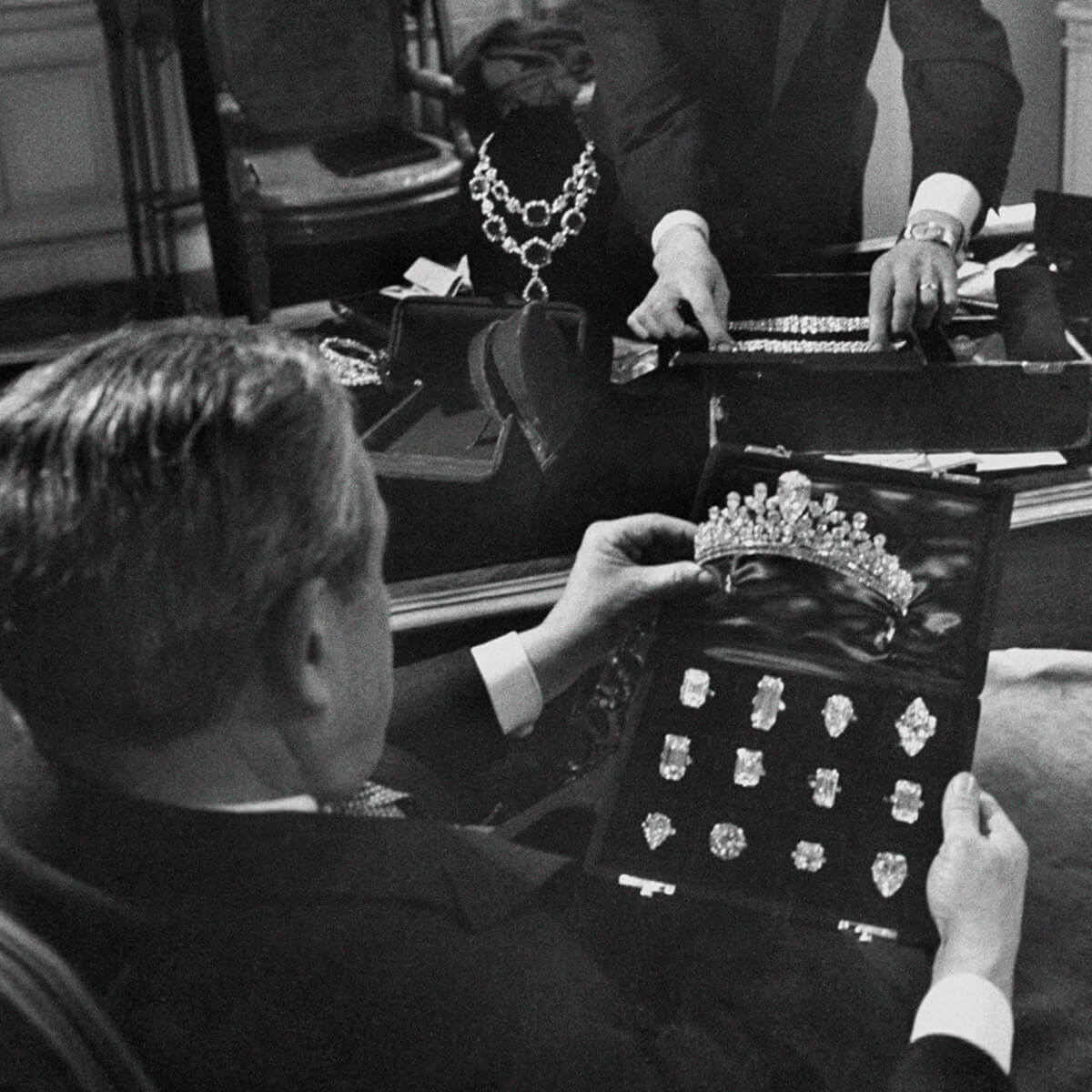 A black and white image of Mr. Winston at his desk with a variety of diamond rings and a diamond tiara