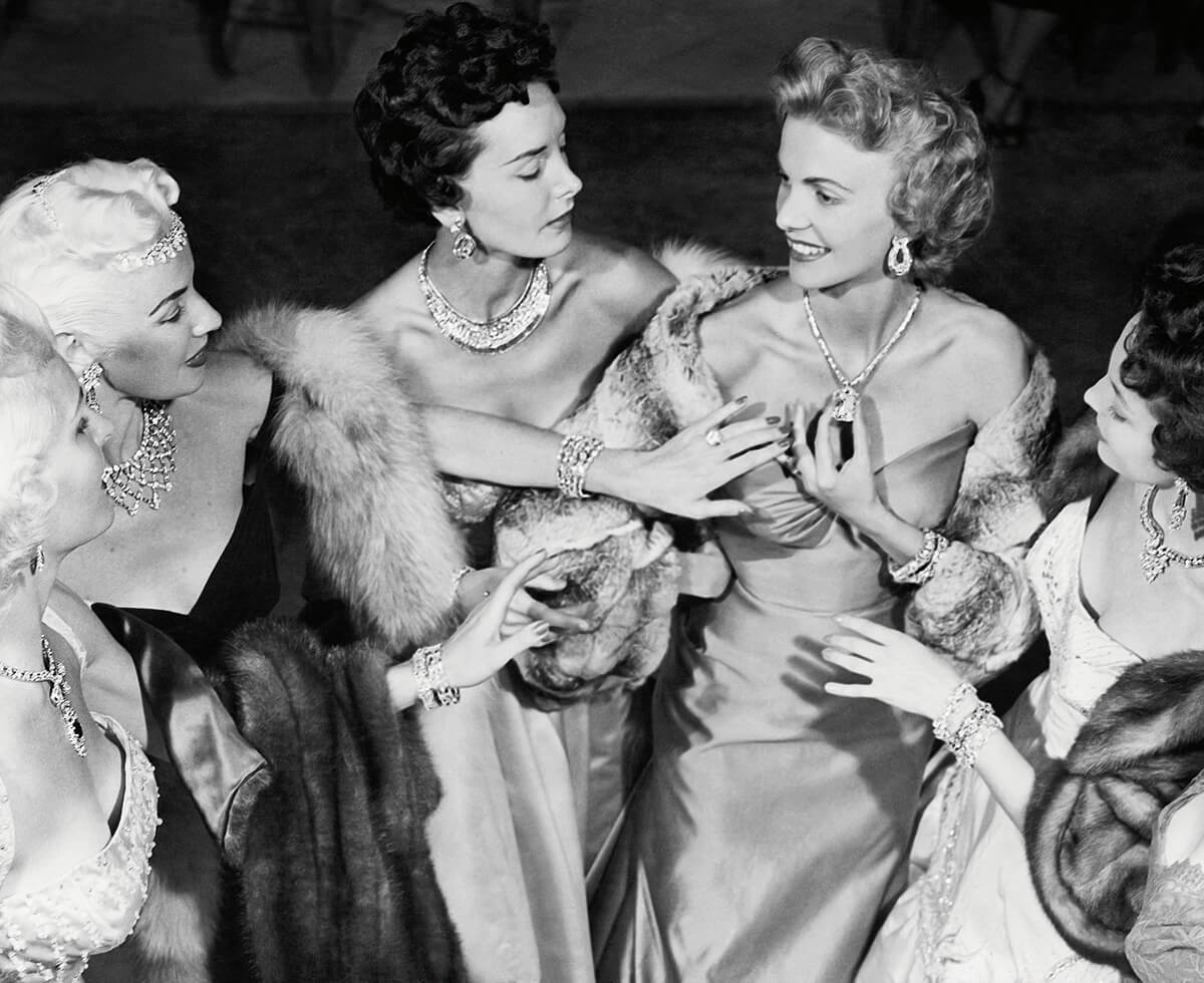 A black and white image shows a group of women adorned in jewelry admiring one another's magnificent necklaces and rings at Harry Winston's Court Of Jewels